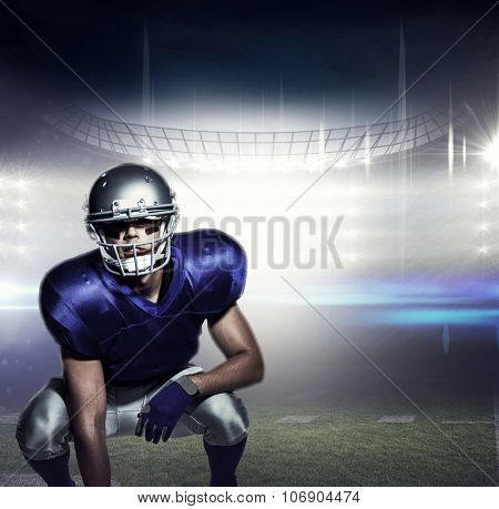 American football player in uniform crouching against american football arena