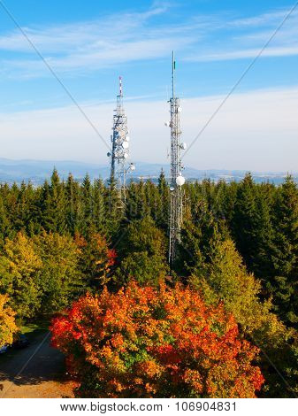 Two transmission towers in autumn forest