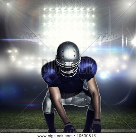 American football player holding ball while crouching against american football arena