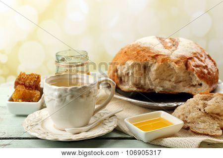 Honeycomb, bowl with honey, cup with herbal tea on color wooden table, on light background