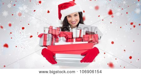 Smiling brunette in santa hat holding stack of presents against snowflake pattern