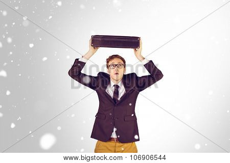 Young geeky businessman holding briefcase against snow