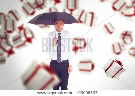 Businessman standing under black umbrella against white and red gift box