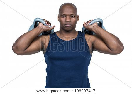 Muscular man exercising with kettlebell on white background