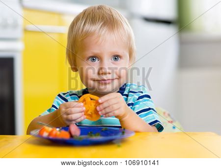 Cute little boy eats his lunch sitting at a table in the kitchen