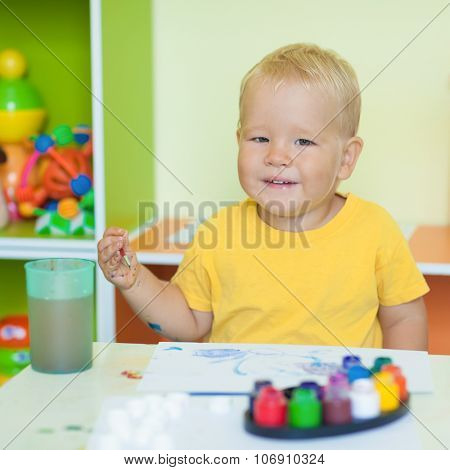 Toddler boy practice to paint on paper sitting at the table in child room