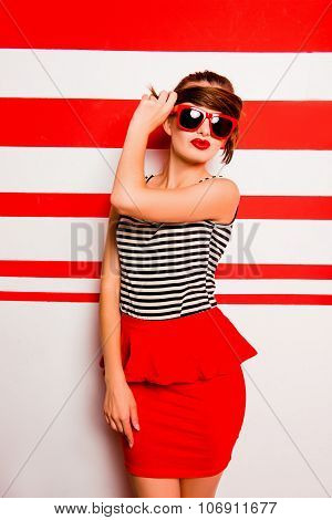 Cute Girl With Red Lips And Glasses Posing Against The Striped Background