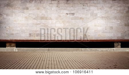 Weathered cinder block, brick wall texture with sidewalk.