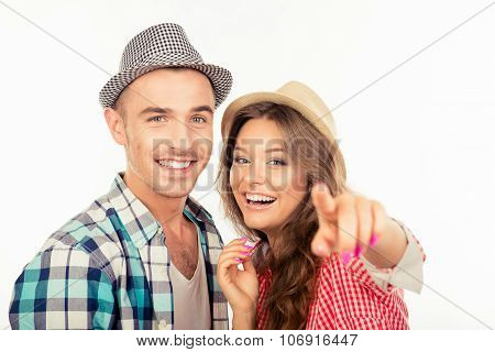 Cheerful Pretty Couple In Love With Hats Pointing The Camera