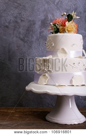 White wedding cake decorated with flowers on wooden table against grey background