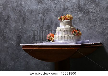 Wedding cake decorated with flowers on grey background
