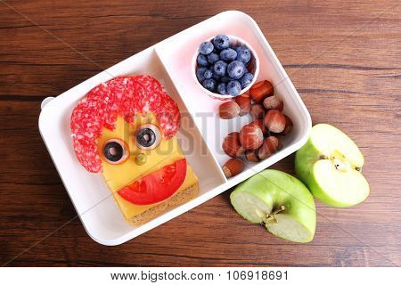 Lunchbox with creative sandwich and fruits on wooden background
