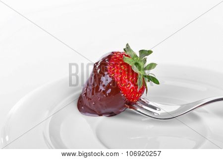 A fork and a strawberry in chocolate isolated on white
