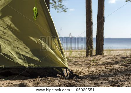 edge of tourist tents, which stands on a sandy beach near the water