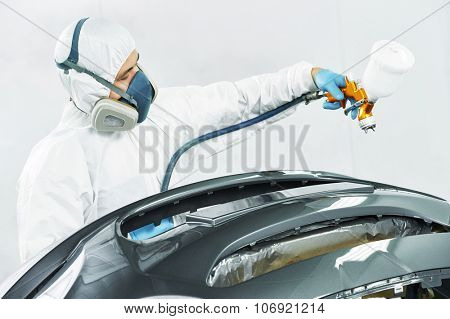 auto mechanic worker painting auto car bumper in a paint chamber during repair work