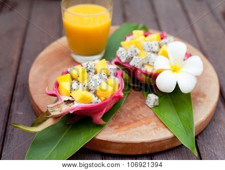 Tropical fruit salad in pitahaya, dragon bowls with mango juice.