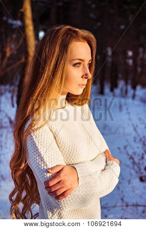 Portrait Of A Pretty Girl In White Pullover In Winter Forest