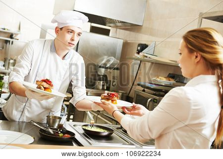 young male cook chef in white uniform gives to waitress plates with prepared meal in commercial kitchen