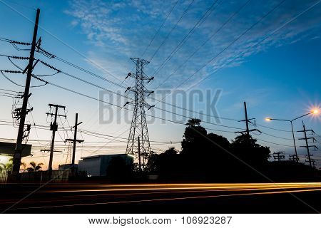 Power transmission tower during twilight time And car lights