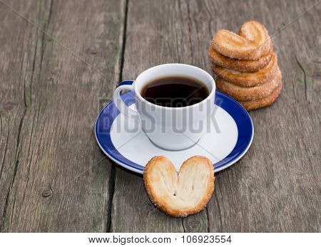 Coffee On A Saucer, And A Column From Cookies, On A Wooden Table