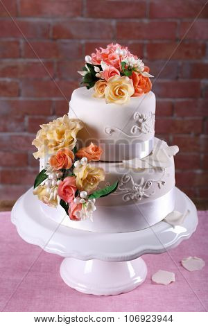 Beautiful wedding cake decorated with flowers on pink table against brick wall background