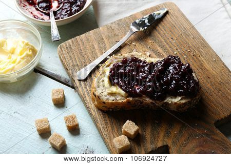 Tasty jam in the bowl, butter, fresh bread and crackers on blue wooden background