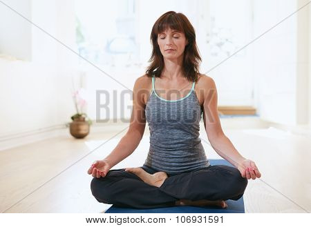 Fit Woman In A Meditative Yoga Pose At Gym