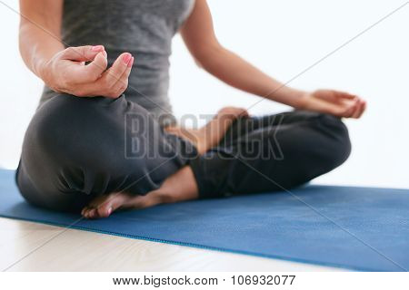 Woman In Lotus Pose On Exercise Mat At Gym