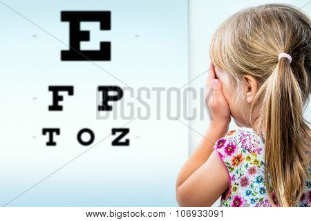 Rear View Of Girl Testing Eyesight.