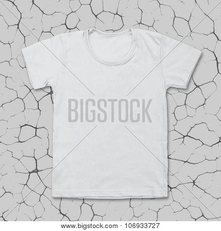 White blank t-shirt on dark cracked desk.