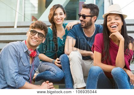 Closeup shot of young friends sitting on staircase having fun. Happy girls and guys smiling and looking at camera. Young men and young women stay together.