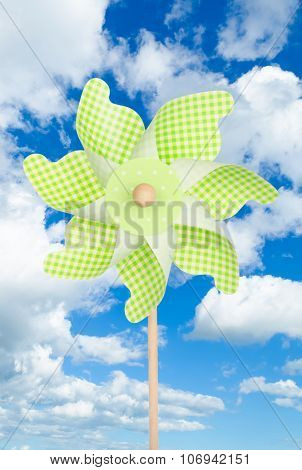 Colorful Green Pinwheel Over Blue Sky With Clouds