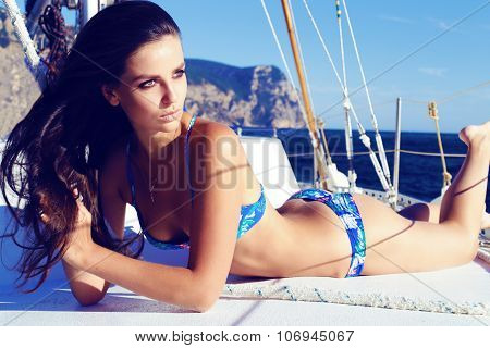 Beautiful Woman Wears Blue Bikini, Relaxing On Yacht In The Sea