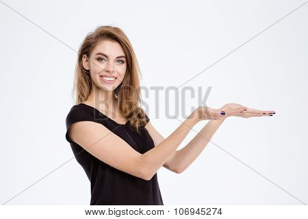 Portrait of a smiling young woman holding copyspace on the palms isolated on a white background