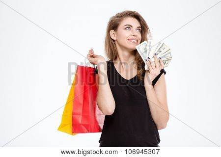 Portrait of a happy woman holding shopping bags and money isolated on a white background