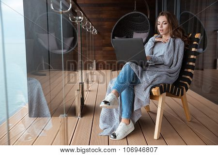 Amazed beautiful woman sitting wrapped in gray knitted coverlet using laptop