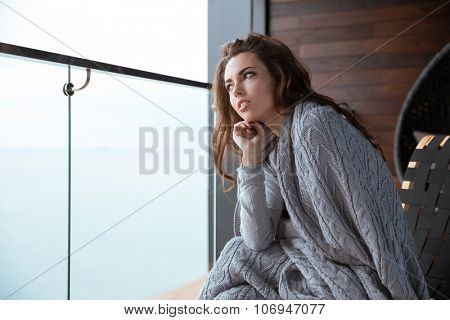 Young beautiful woman sitting wrapped in gray knitted coverlet and thinking