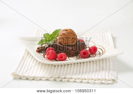 brownie cake with scoop of chocolate ice cream and raspberries on white plate and place mat