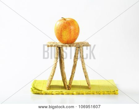 sesame seed crispbread and ripe apple arranged on green place mat