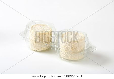 package of two soft white rind cheeses on white background