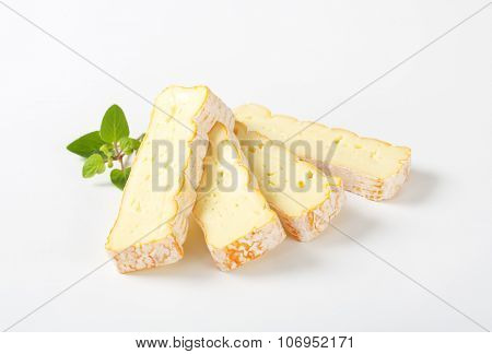 sliced soft white rind cheese on white background