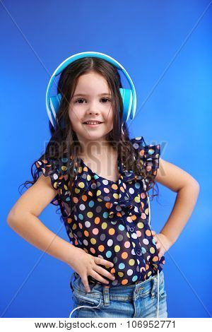 Happy little girl in colourful shirt with headphones on blue background