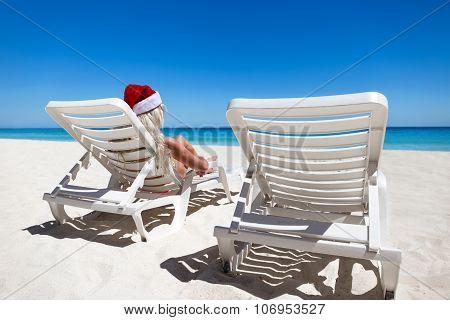 Woman In Santa Claus Hat Sitting On Sunbed At Caribbean Sandy Beach