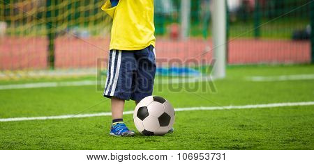 Child is kicking soccer ball. Kid playing football soccer match