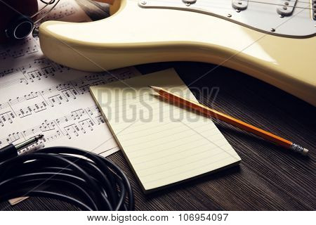 Electric guitar with musical notes, pencil and sheet on wooden background