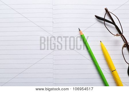 Opened striped note book background with yellow pen and green pencil