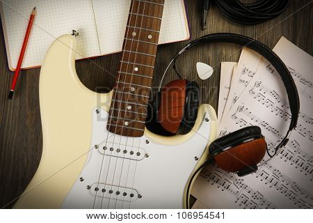 Electric guitar with headphones, musical notes and note book on wooden background