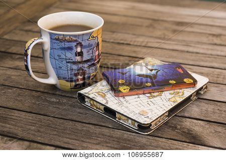 Tea Mug, E-reader And Mobil Phone On A Table