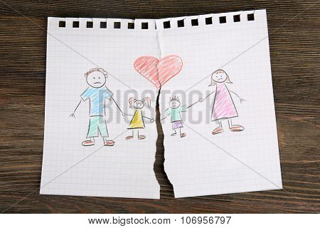 Torn apart drawing of a family on wooden background