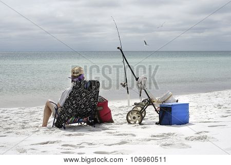 Woman Fishing On Overcast Day At The Beach